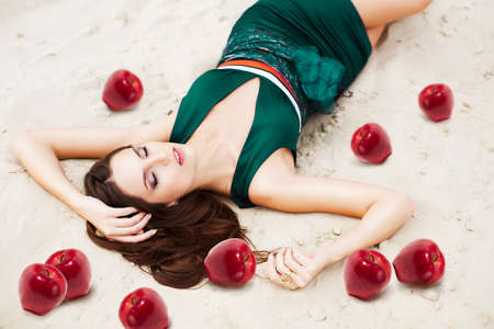woman with red apples on the sand in green dress photo