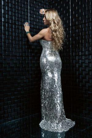 Beautiful blonde in brilliant silver dress photo