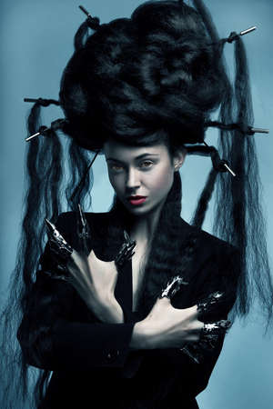 Gothic style shot of a woman with claw rings and blue tint photo