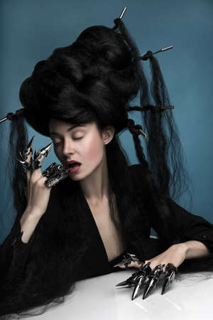 Gothic style shot of a woman with claw rings sitting at the table photo