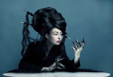 Gothic style shot of a woman with claw rings and blue tint sitting at the table photo