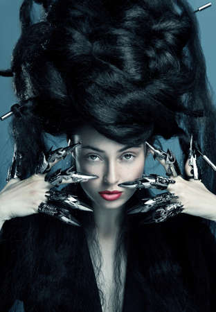 Gothic style shot of a woman with claw rings and blue tint touching face photo
