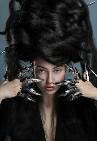 Gothic style shot of a woman with claw rings touching face photo