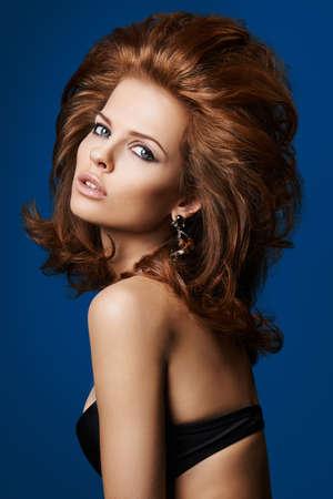 lussureggiante: Ritratto di una donna con i capelli rigogliosa su sfondo blu