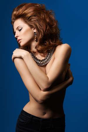 lussureggiante: Donna con capelli rigogliosa e una collana su sfondo blu Archivio Fotografico