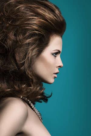 파란색 배경 프로필에 무성 한 머리를 가진 여자