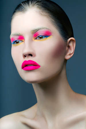 Beautiful girl with pink make up on blue background photo