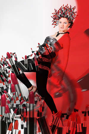 Girl with lipsticks around and on the head and red background photo