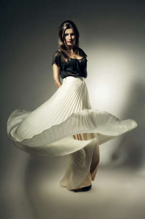 pretty woman with long flying skirt Stock Photo