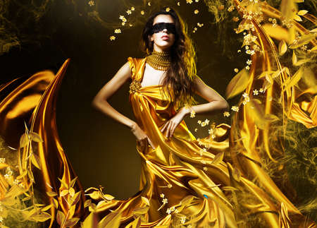 sensual adult woman in golden fabric and mask with leaves 스톡 콘텐츠
