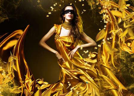 sensuele volwassen vrouw in gouden stof en masker met bladeren