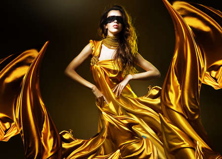 sensual adult woman in golden fabric and mask photo