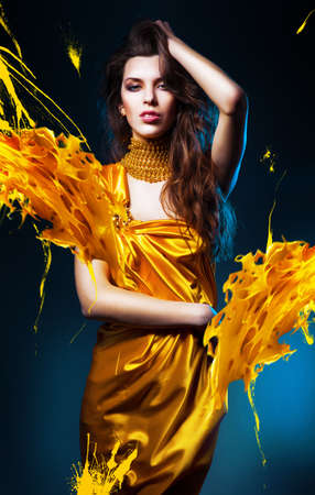 sensual sexy woman in yellow dress and yellow splash photo