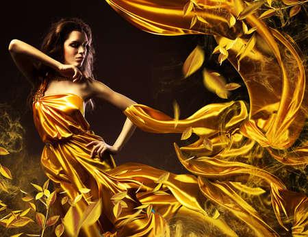 mujer sexy: mujer sexy delgada en tela amarilla y hojas Foto de archivo