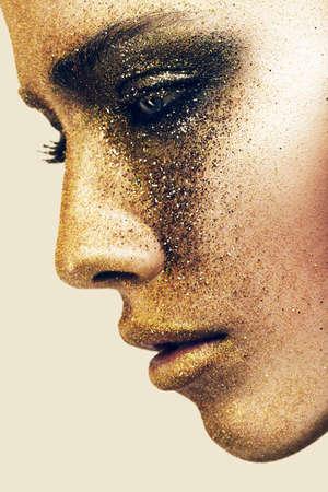 ojos marrones: cara de la mujer en brillos de oro