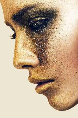 gold facial: woman face in gold glitters