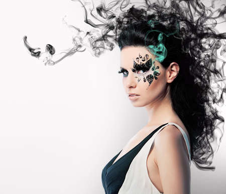 face art of rhinestones on brunette woman and smoke Banque d'images