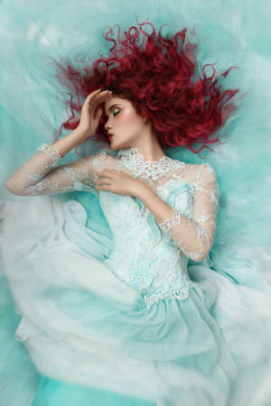 fashion girl lying in a turquoise dress photo