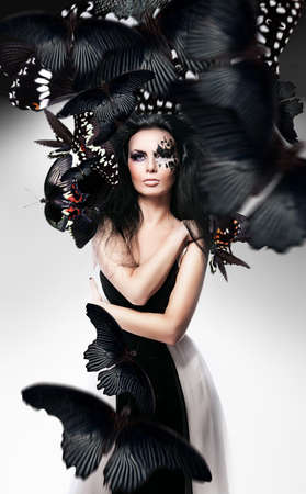elegance fashion girls look sensuality young: Woman with black hair and art make up and black butterflies