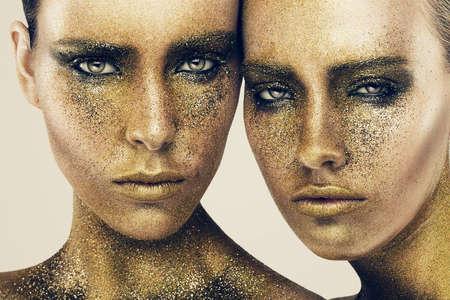 women faces in gold glitters 写真素材