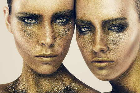 glitter makeup: women faces in gold glitters Stock Photo