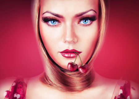 blond woman with blue eyes and cherry in mouth photo