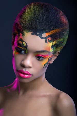 Beautiful african woman with creative neon make up on dark blue background