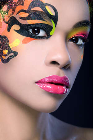 Portrait of an african beauty with exotic make up on dark blue background