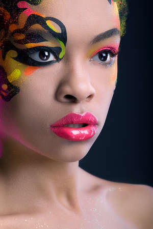 Portrait of a pretty african girl with neon make up on dark blue background photo