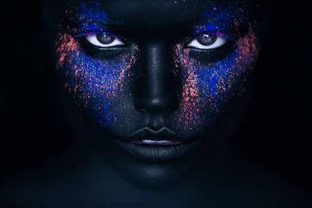 meisje in zwarte verf en neon poeder Stockfoto