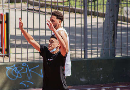 Madrid / Spain - 07 13 20: A young man with his mask on his chin and jumping on the summer. He is playing basketball.
