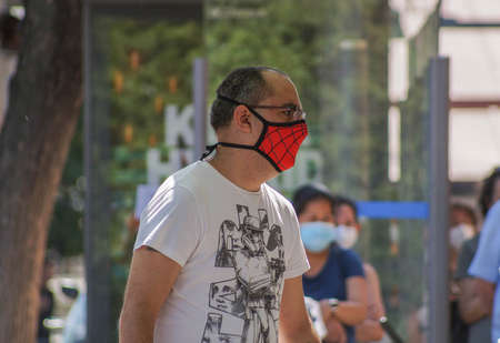 Madrid / Spain - 07 13 20: A man with original Spiderman face mask during the pandemic of Covid-19 in the street of Madrid in the summer