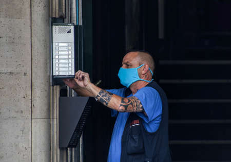 Madrid / Spain - 07 13 20: electrician is working and wearing a blue mask outside a building