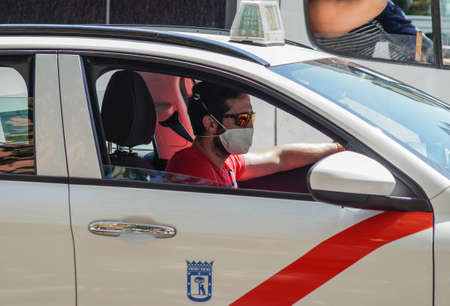 Madrid / Spain - 07 13 20: Taxi driver in the summer working with the new health situation and wearing a face mask 新闻类图片