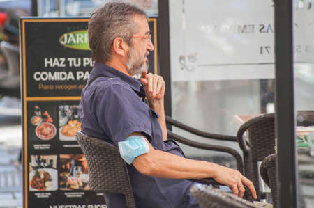 Madrid / Spain - 07 13 20: Man sitting in a terrace is doing a bad use of a face mask, is on his elbow