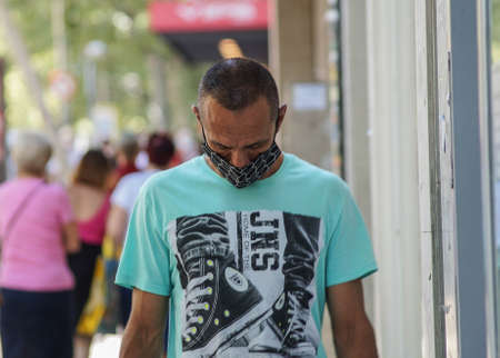 Madrid / Spain - 07 13 20: Man walking on the street wearing a beautiful face mask during pandemic situation in Madrid 新闻类图片