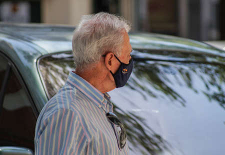 Madrid / Spain - 07 13 20: retired man on the street wearing a dark face mask in the new coronavirus situation