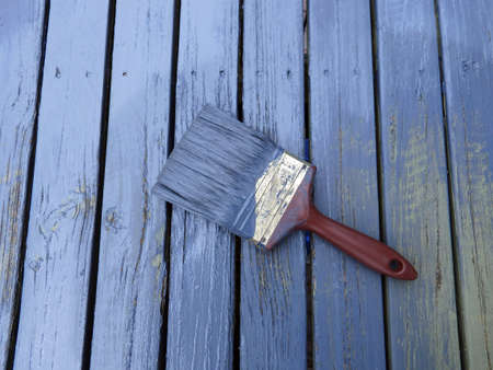 Paint brush and deck with fresh paint