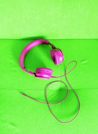 pink headphones on super green background