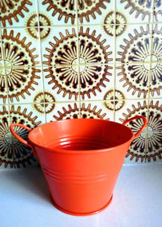 Orange tin bucket piece in vintage kitchen
