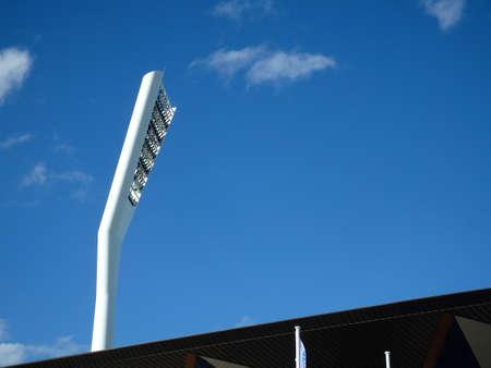 Giant futuristic modern, white  tower with stadium lights