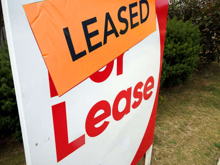 House for lease sign in front of a home with the leased sticker Stock Photo