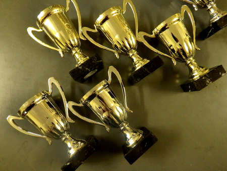 Collection of golde trophy cups in gray background