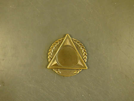 Single triangular shaped medal made of golden metal