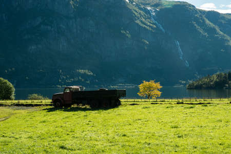 transport truck: An old track in a grass field next to a beautiful waterfall, Norway