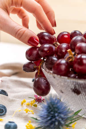 Detail of woman's hand picking one red grape on a crystal bowl with blueberries, some wild flowers and a cloth