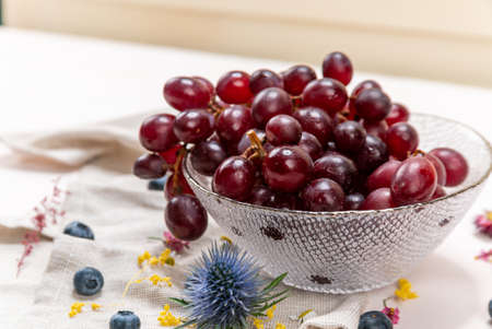 Red grapes on a crystal bowl with blueberries, some wild flowers and a cloth