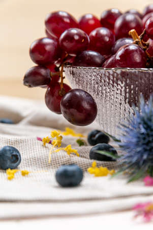Detail of some red grapes on a crystal bowl with blueberries and some wild flowers