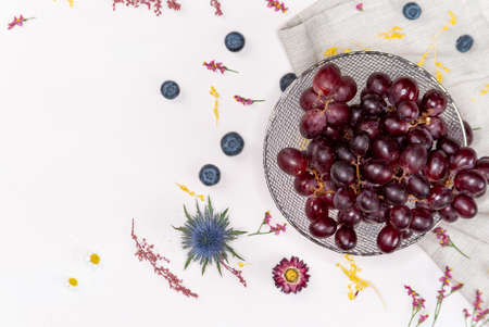 Red grapes on a bowl from above on a side with blueberries and some wild flowers
