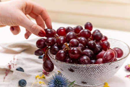 Woman's hand picking one red grape on a crystal bowl with blueberries, some wild flowers and a cloth 免版税图像